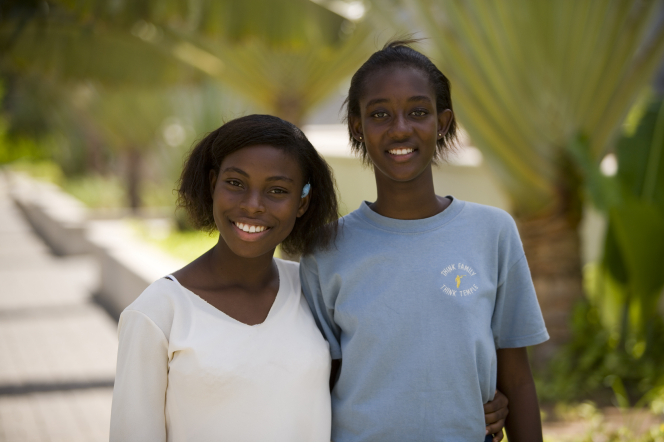 A portrait of two young women smiling and standing outside with their arms around one another.