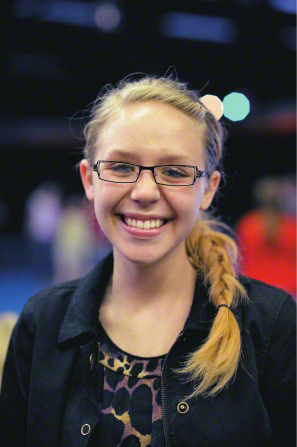 A young woman with glasses and a long blonde braid, smiling.