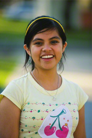 A young woman in Mexico, wearing a yellow shirt with pink cherries on it, smiling.