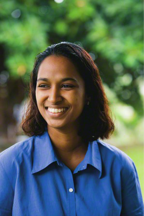 A young woman in Fiji with short, black, wavy hair and a blue buttoned shirt, smiling.