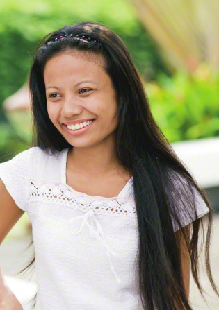 A young woman outside in the Philippines, with long black hair and a white shirt, looking to the side and smiling.
