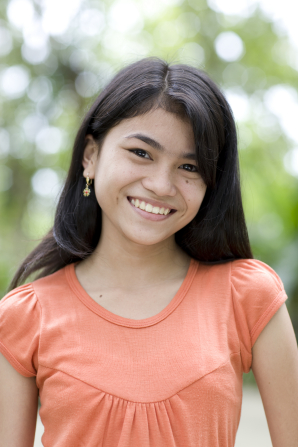 A portrait of a young woman from the Philippines with dark brown hair and an orange shirt, standing outside and smiling.