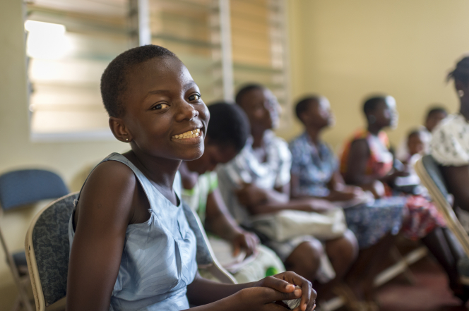 A young girl in a blue dress sits in Sunday School with other youth and smiles.