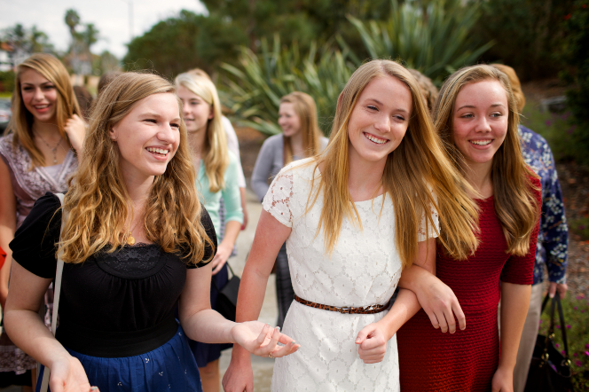 A group of young women link arms and walk together outside, smiling.