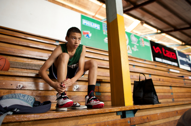 A young man wearing a basketball uniform sits on wooden bleachers, warming up, preparing to go out on the court.