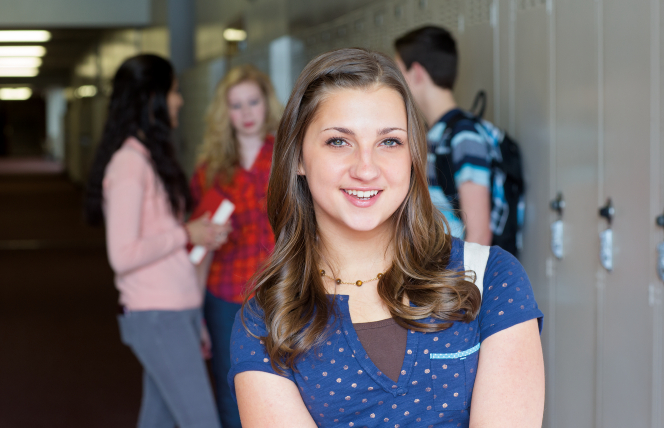 A young woman smiles, standing near lockers in a high school, with three other teenagers standing in the hallway behind her.